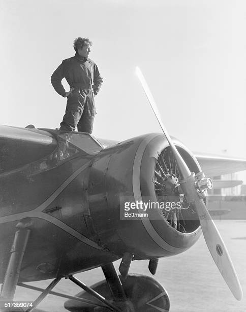 Portrait of American aviatrix Amelia Earhart the first woman to cross the Atlantic Ocean in an airplane She is shown here standing atop her plane...