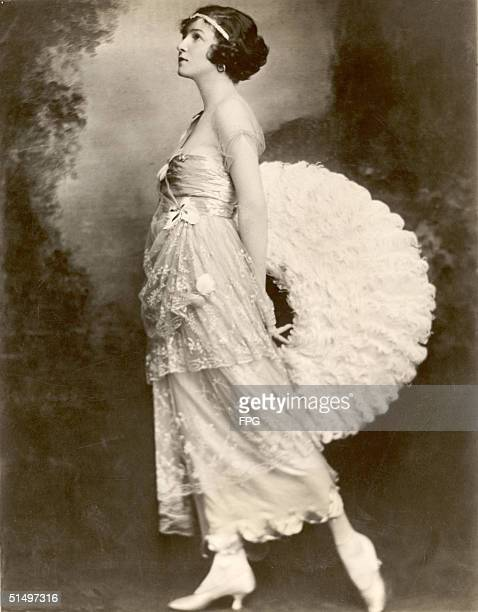 Portrait of American ballroom dancing legend and actress Irene Castle as she poses with a large white fan of feathers behind her back New York 1918