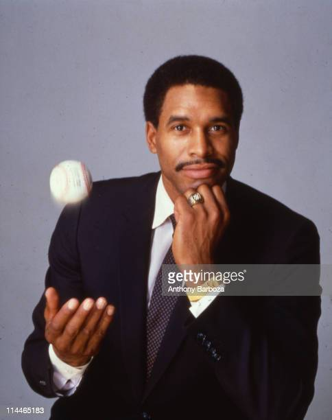Portrait of American baseball player Dave Winfield of the New York Yankees dressed in a suit and tie as he throws a baseball into the air 1980s