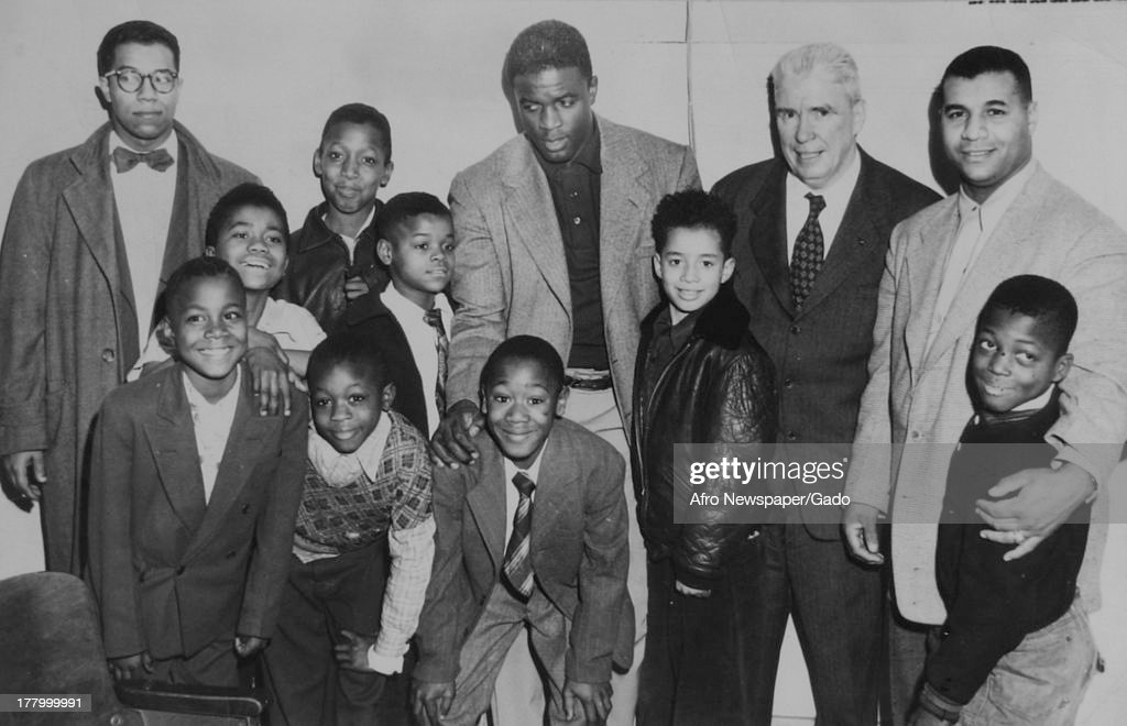 Portrait of American baseball player Jackie Robinson (1919 - 1972), of the Brooklyn Dodgers, as he poses with teammate Roy Campanella (1921 - 1993) (right), two other men and a group of children, 1950.