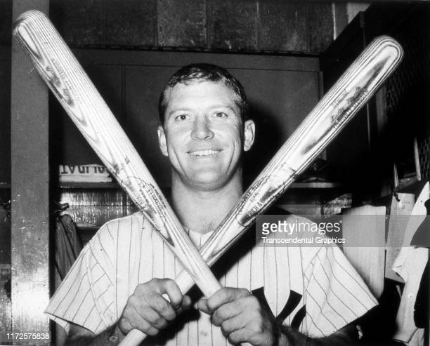 Portrait of American baseball player Mickey Mantle of the New York Yankees as he poses a pair of crossed baseball bats in the team's clubhouse New...