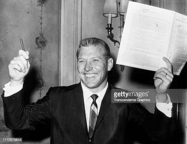 Portrait of American baseball player Mickey Mantle of the New York Yankees as he poses with his new annual team contract New York New York 1961