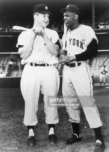Portrait of American baseball players Mickey Mantle of the New York Yankees and Willie Mays of the New York Giants as they pose together before a...