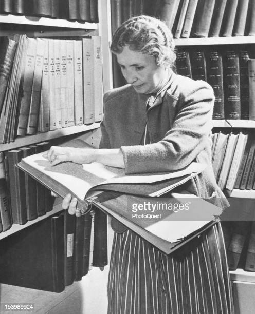 Portrait of American blind and deaf author and activist Helen Keller as she reads a book in braille in a library 1950