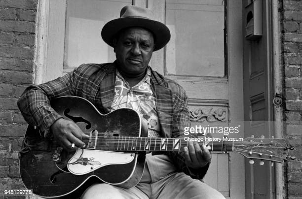 Portrait of American Blues musician Big Joe Williams a guitar in his hands as he sits on his front porch in the South Side neighborhood Chicago...