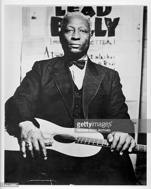 Portrait of American Blues musician Lead Belly as he poses with a guitar on his lap, 1940s.