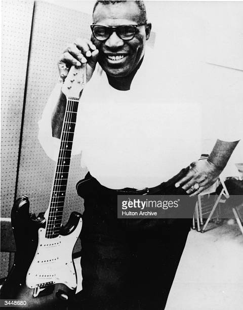 Portrait of American blues singer and songwriter Howlin' Wolf smiling beside an electric guitar, 1960s.