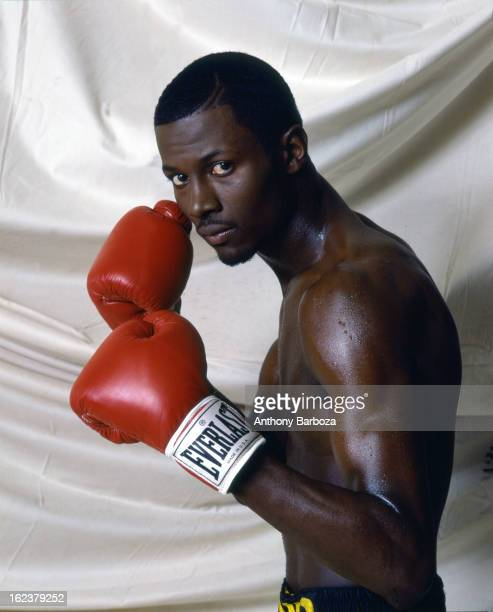 Portrait of American boxer and Olympic gold medalist Mark Breland as he poses, against a backdrop curtain, with his red boxing gloves raised, 1980s.
