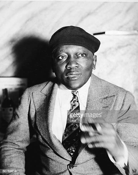 Portrait of American boxer heavyweight champion and inventor Jack Johnson smoking a cigar circa 1930s