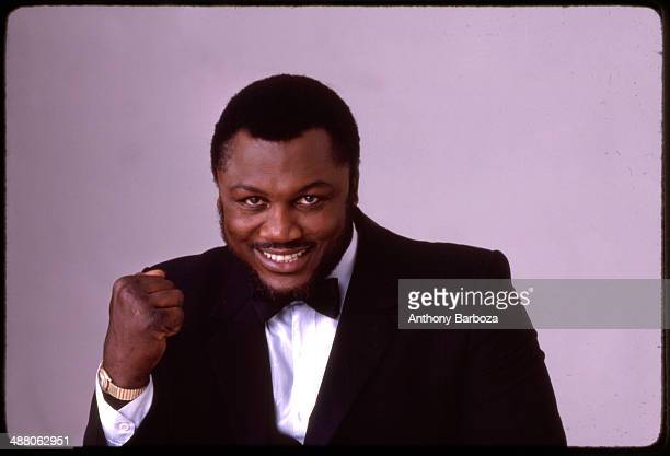 Portrait of American boxer Joe Frazier dressed in a tuxedo and bowtie as he smiles while holding his right fist raised New York 1983