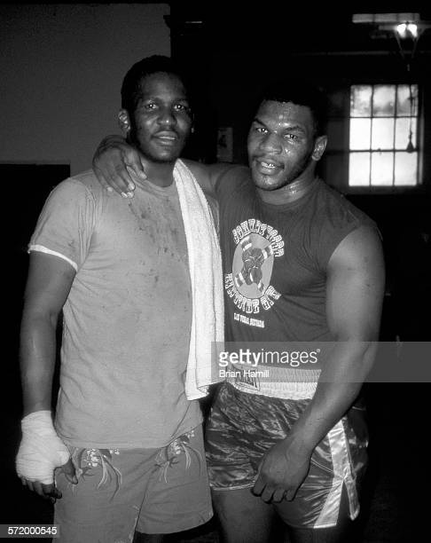 Portrait of American boxer Mike Tyson as he poses with an unidentified boxer while training New York April 1987