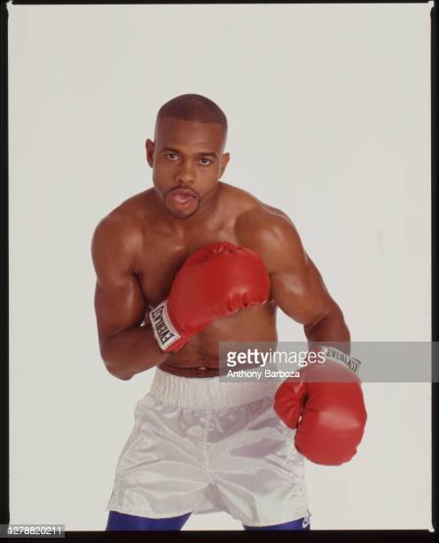Portrait of American boxer Roy Jones Jr as he poses, against a white background, dressed in boxing gloves and shorts, New York, New York, 1997.