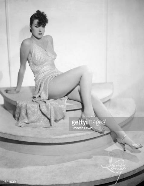 Portrait of American burlesque performer and author Gypsy Rose Lee seated on a pedestal wearing a slit gown circa 1938