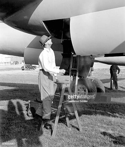 Portrait of American businessman and aviator Howard Hughes on a stepladder beneath one of his airplanes, Los Angeles, California, 1947.