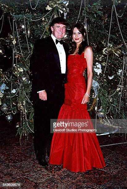 Portrait of American businessman Donald Trump and model Melania Knauss as they pose together in front of a Christmas tree at the MaraLago estate Palm...