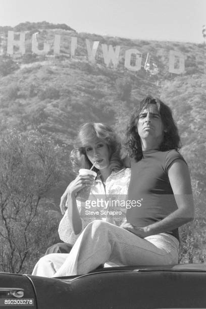 Portrait of American choreographer Sheryl Cooper and her husband musician Alice Cooper as they sit in a convertible beneath the 'Hollywood' sign Los...