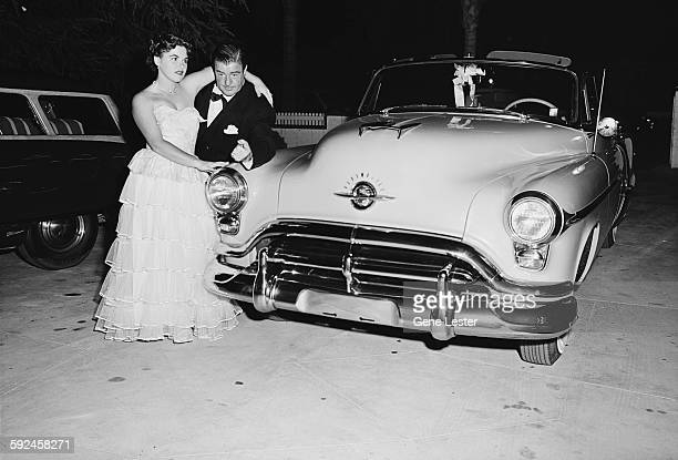 Portrait of American comedian and actor Lou Costello and an unidentified woman as they pose beside an Oldsmobile in the parking lot September 27 1952...