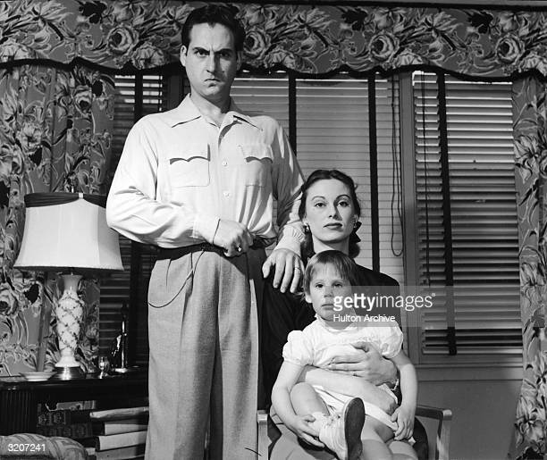 Portrait of American comedian and actor Sid Caesar making a funny face while standing next to his wife Florence and their daughter Karen