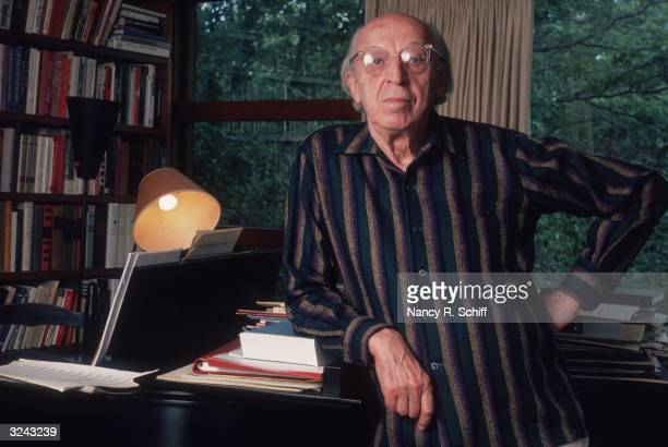 Portrait of American composer Aaron Copland leaning against a piano with one hand on his hip at his home