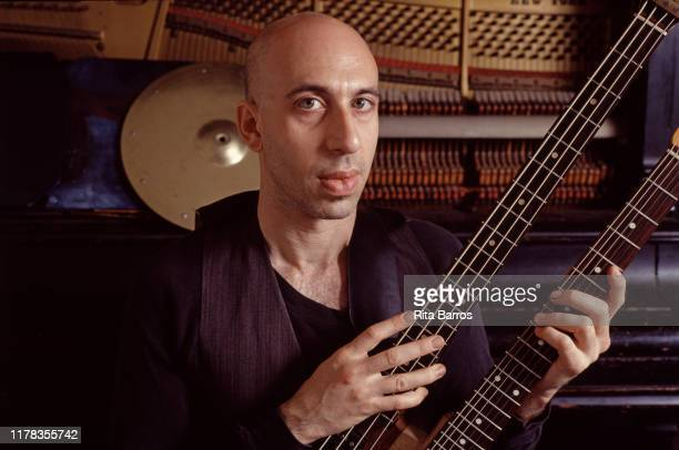 Portrait of American composer and musician Elliott Sharp as he poses with a twin-necked bass guitar at the Knitting Factory, New York, New York, 1990.