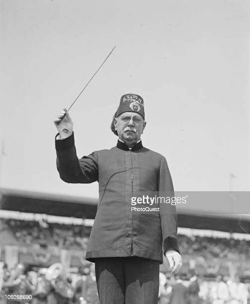 Portrait of American composer John Philip Sousa holding a raised baton June 1923