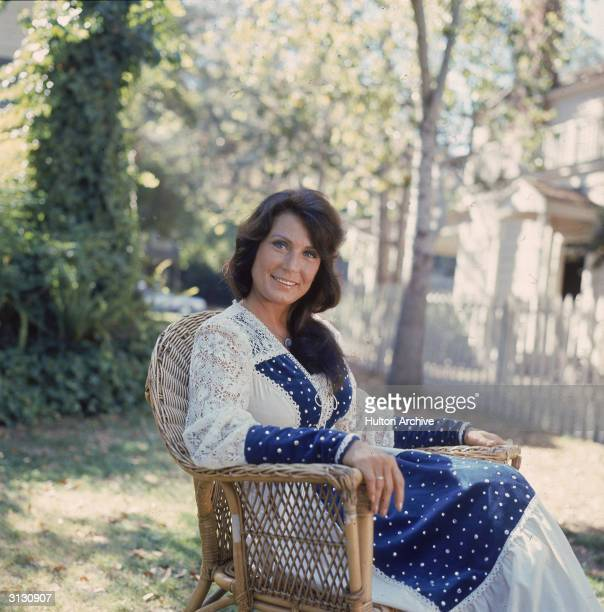 Portrait of American country music singer and guitarist Loretta Lynn as she sits outside in a chair 1970s