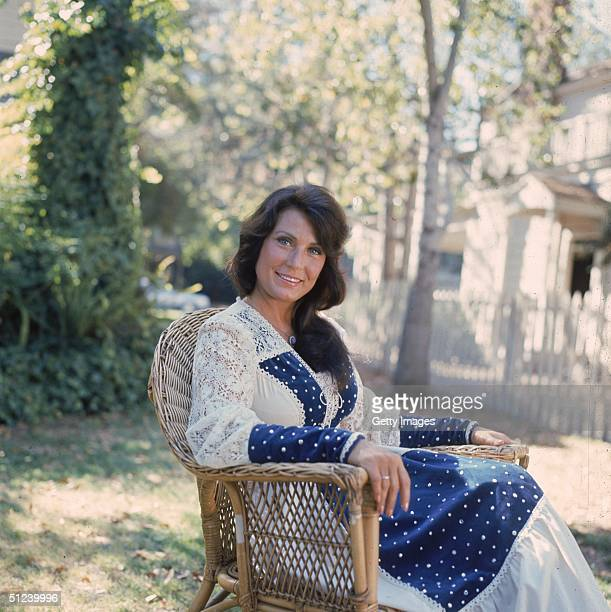 1978 Portrait of American country music singer and musician Loretta Lynn sitting outdoors in a lace dress
