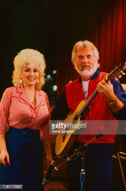 Portrait of American Country musicians Dolly Parton and Kenny Rogers on guitar as they poses on stage Los Angeles California 1983