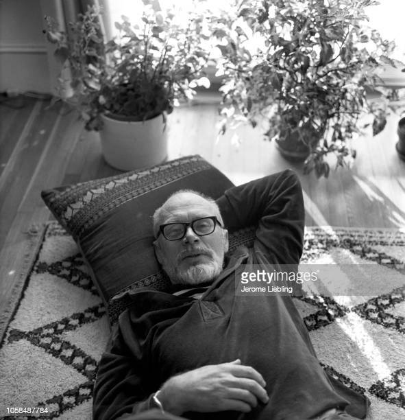 Portrait of American craft potter and University of Minnesota professor emeritus Warren MacKenzie his head on a pillow as he reclines on a rug...