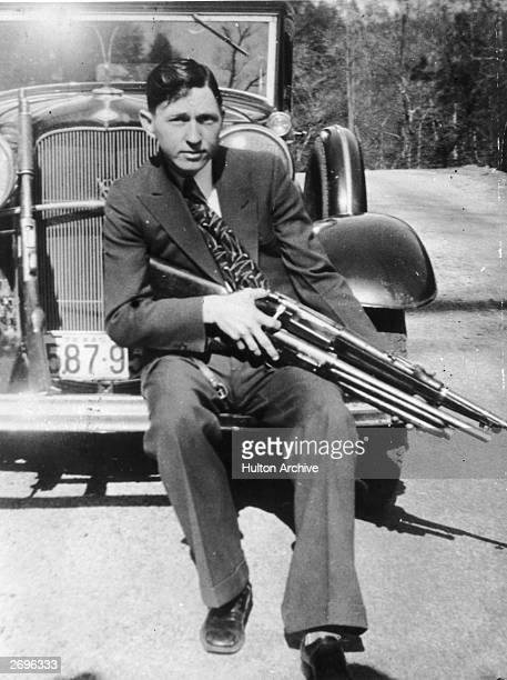 Portrait of American criminal Clyde Barrow holding a machine gun while sitting on the front fender of a car.