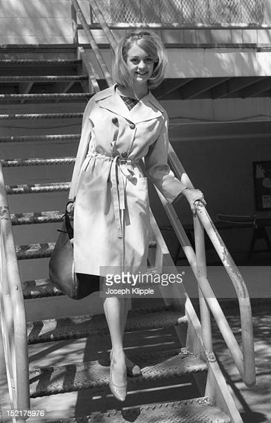 Portrait of American dancer and dance instructor and future actress Goldie Hawn dressed in a belted doublebreasted trench coat smiles as she poses on...