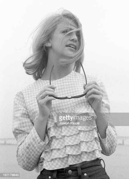 Portrait of American dancer and dance instructor and future actress Goldie Hawn holds a pair of sunglasses as she poses in a ruffled gingham top...