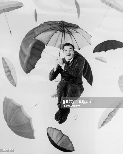 Portrait of American dancer singer and actor Gene Kelly jumps in the air while holding an umbrella in front of a backdrop painted with umbrellas in a...