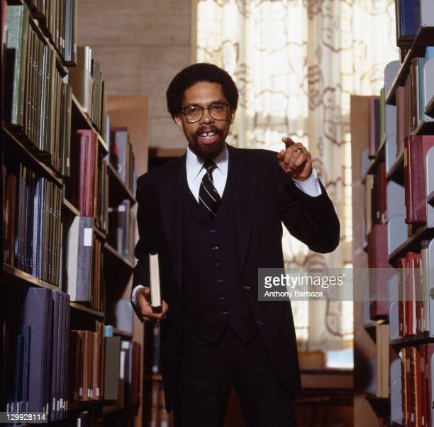 Portrait of American educator activist and author Cornel West as he stands in the stacks of the library of Princeton University where he is a...