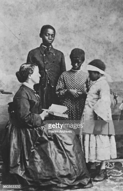 Portrait of American educator Laura Matilda Towne , seated with students Dick Washington, Maria Wyne, and Amoretta, South Carolina, February 1866....