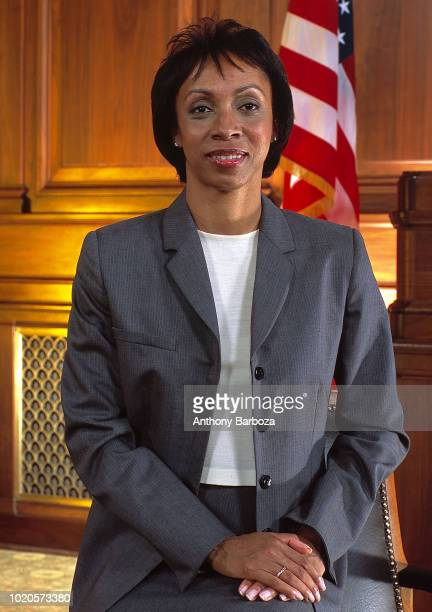 Portrait of American entertainment and sports talent attorney Nina Shaw as she poses in front of an American flag California 1990s