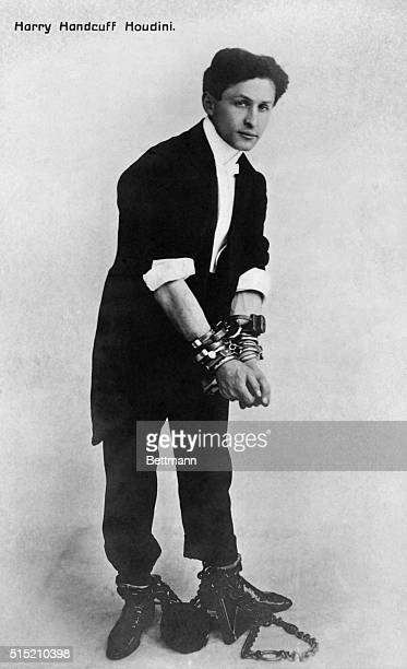 Portrait of American escape artist Harry Houdini dressed in a tuxedo and bound by ankle shakles and wrist handcuffs Undated photograph