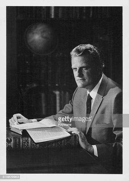 Portrait of American evangelist Billy Graham sitting in a library with a book circa 1970