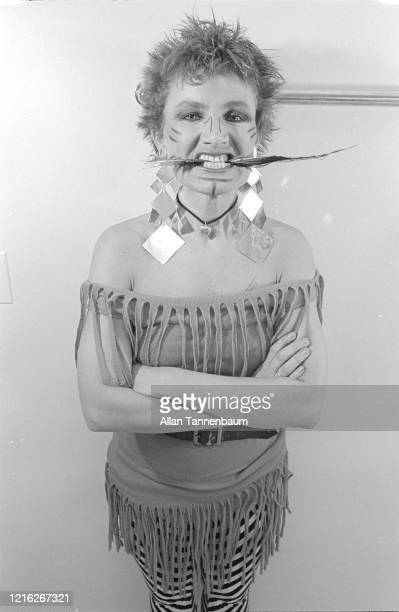 Portrait of American fashion designer Betsey Johnson as she clenches a feather between her teeth posing in her studio New York New York July 9 1980
