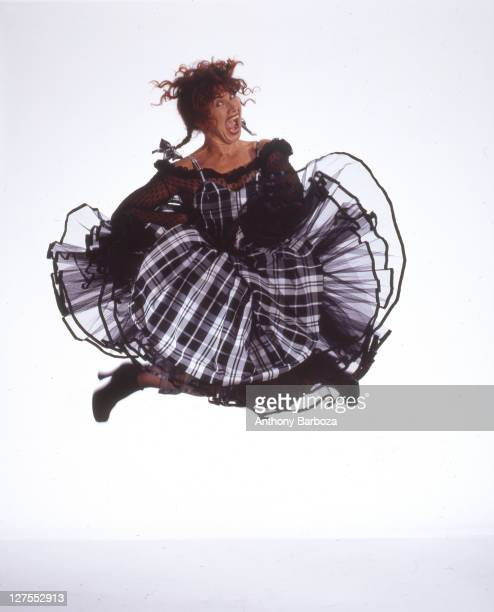 Portrait of American fashion designer Betsey Johnson dressed in black and white tartan and lace in midair as she makes a face late 1980s or early...