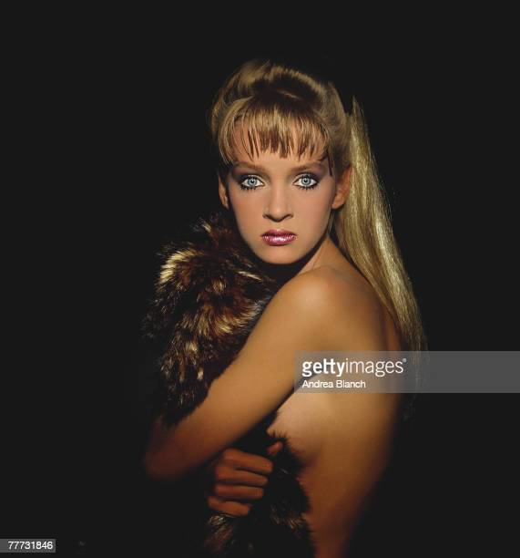 Portrait of American fashion model and film actress Uma Thurman as she poses topless behind a fur coat for an unidentified magazine photoshoot mid...