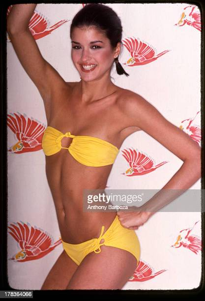 Portrait of American fashion model Janice Dickinson as she poses in a yellow, two-piece bathing suit, with one hand on her hip and the other above...