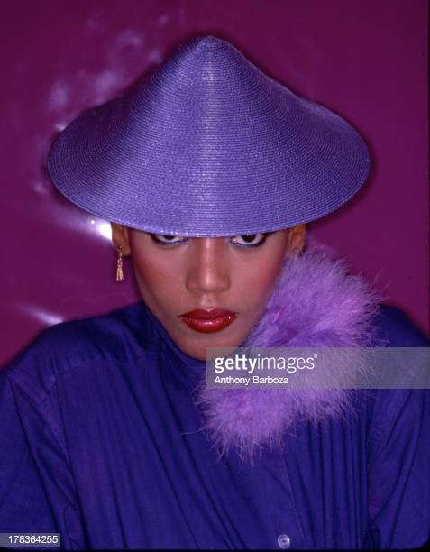 Portrait of American fashion model Toukie Smith as she poses dressed in purple with a matching conical hat New York New York early 1980s