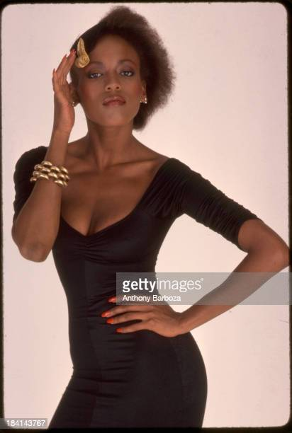 Portrait of American fashion model Toukie Smith as she poses one hand on her hip and the other on her hat against a white background New York New...