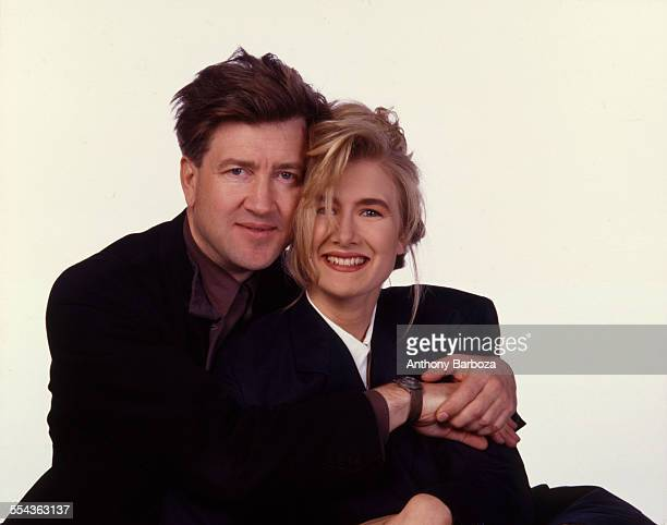 Portrait of American film actress Laura Dern and director David Lynch as they embrace against a white background 1990
