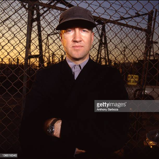 Portrait of American film and television director David Lynch as he poses in front of a chain-link fence, Los Angeles, California, 1989.
