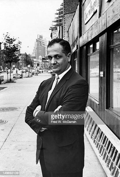 Portrait of American film critic Andrew Sarris as he poses arms crossed outside the offices of the Village Voice newspaper where he worked New York...