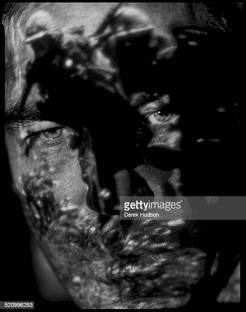 Portrait of American film director Oliver Stone as he poses with a scene from his Vietnam War film 'Platoon' projected onto his face New York 1995...