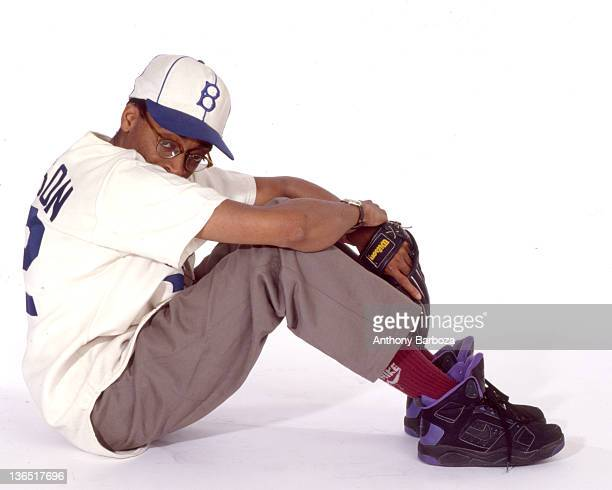 Portrait of American film director Spike Lee , as he sits on the floor, dressed in a baseball cap, jersey, and mitt, New York, New York, 1991.