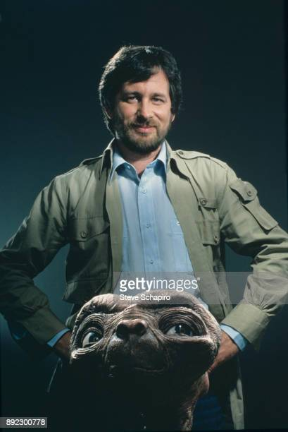 Portrait of American film director Steven Spielberg as he poses hands on his hips with the titular puppet from his film 'ET the Extra Terrestrial'...